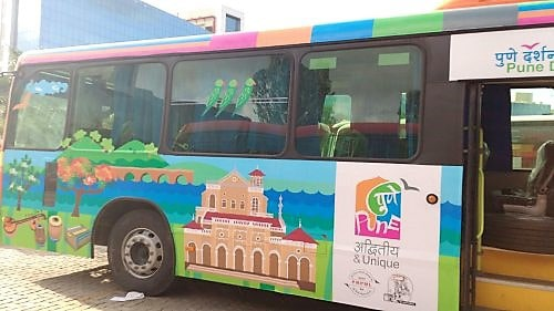 Side view of a Pune Darshan bus covered with printed vehicle graphics depicting scenes of historical monuments in Pune