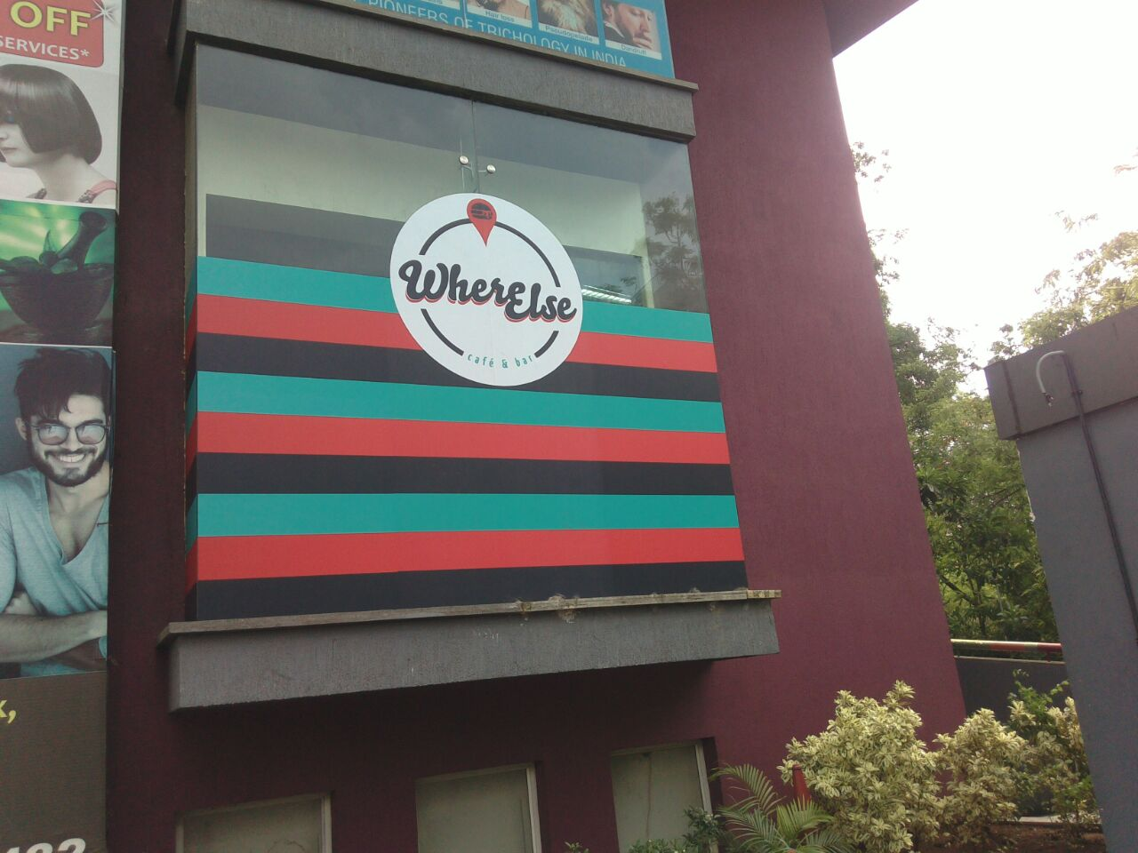 Huge logo of the Where Else Café printed on a film and pasted on the glass frontage of the building