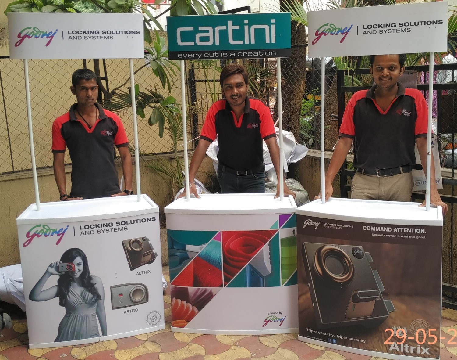 Three exhibition promo tables branded with product images and salesmen standing behind
