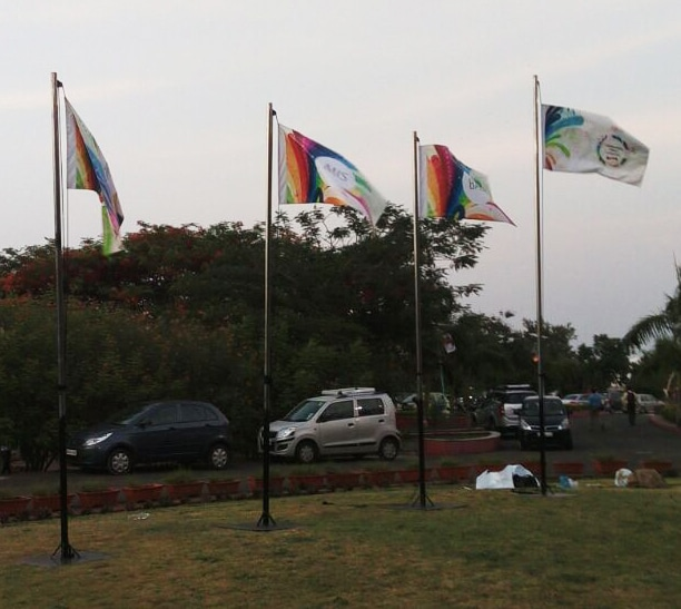 four custom printed flags hoisted on flagpoles billowing in the wind