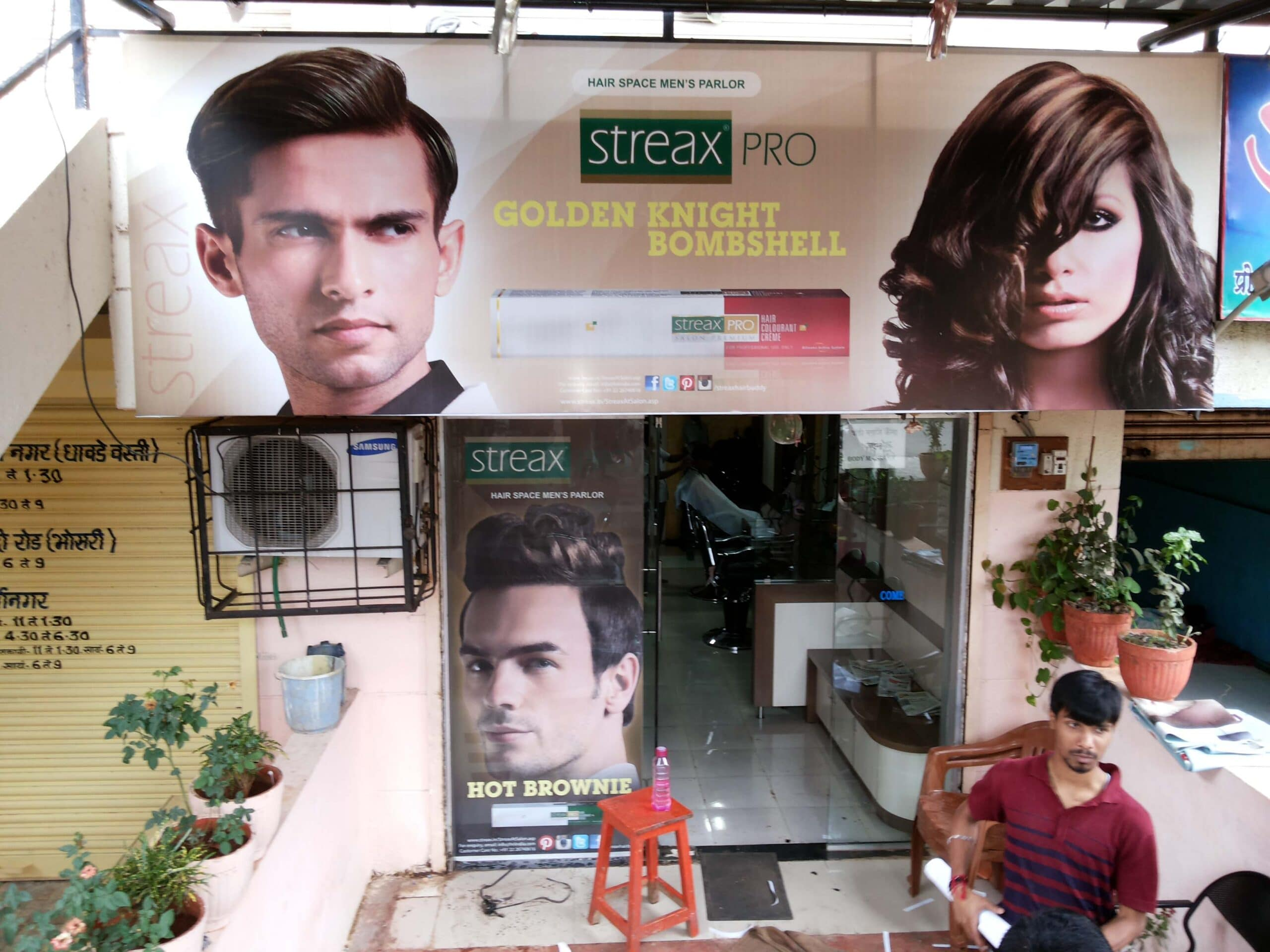 Front lit shop board and glass film prints used for product advertising at the Streax beauty saloon