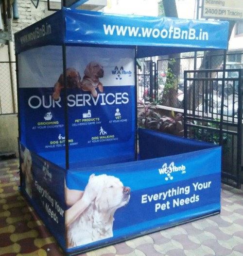 Side view of portable canopy tent branded with services provided by Woof BnB pet care company