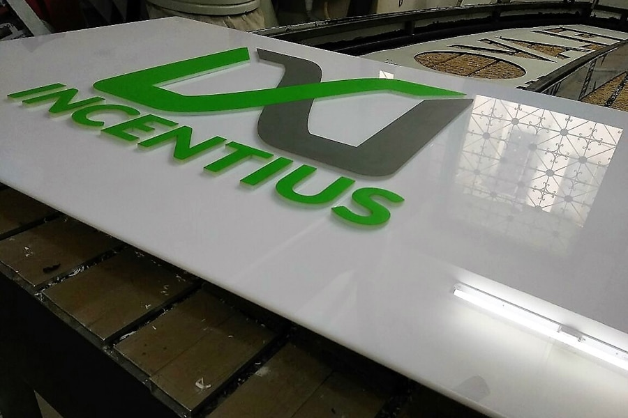 vinyl for logo pasted on white acrylic laser cut letters mounted on white acylic base plate