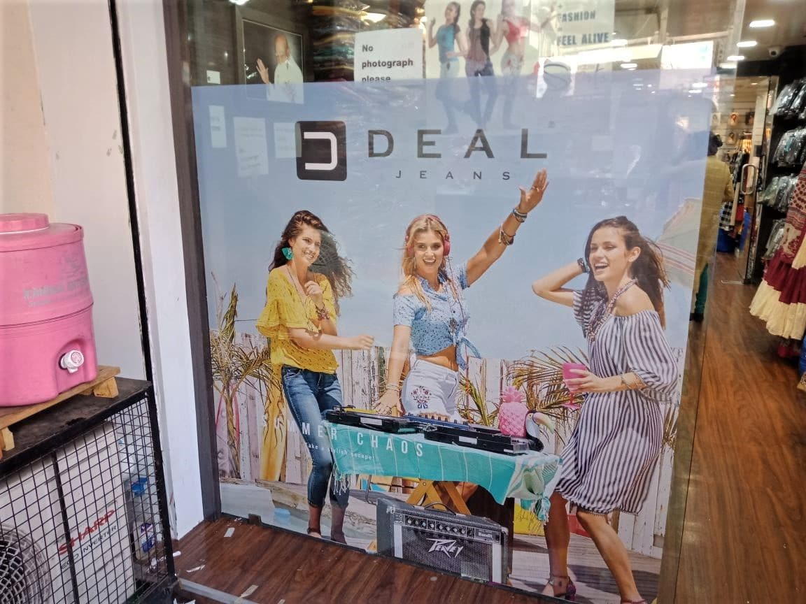 branding on the glass door of a Deal Jeans store using one way vinyl