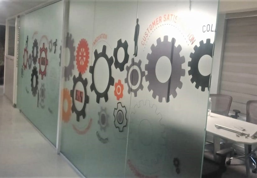 frosted glass film print showing images of gears pasted on the cabin partition of a large office