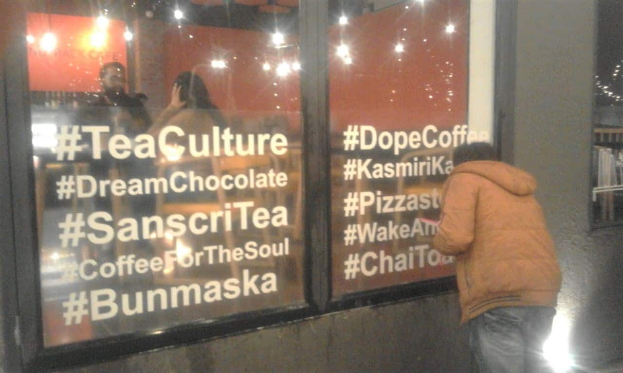 transparent glass print with letters and words in white being pasted by a fitter on the window of a cafe