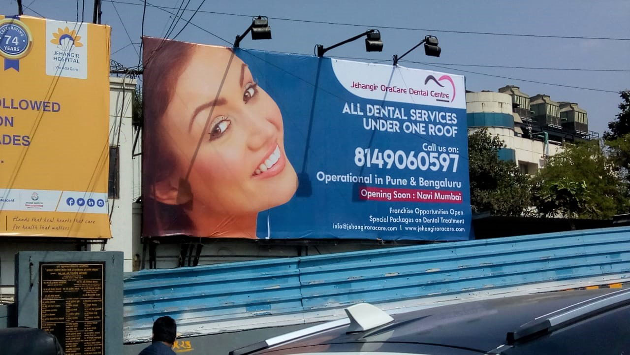 flex printing of a huge hoarding for the Jehangir hospital mounted on the side of a road advertising their dental services