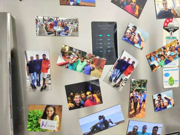 magnets showing vacation photos of a family pasted all over the door of a refrigerator