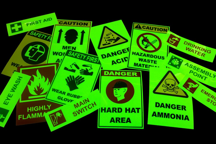glow in the dark safety signs emitting a greenish light in full darkness