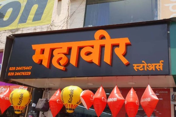 Black ACP base frame with 3D letters fabricated out of orange colored acrylic to create a highly attractive shop board for Mahaveer Stores