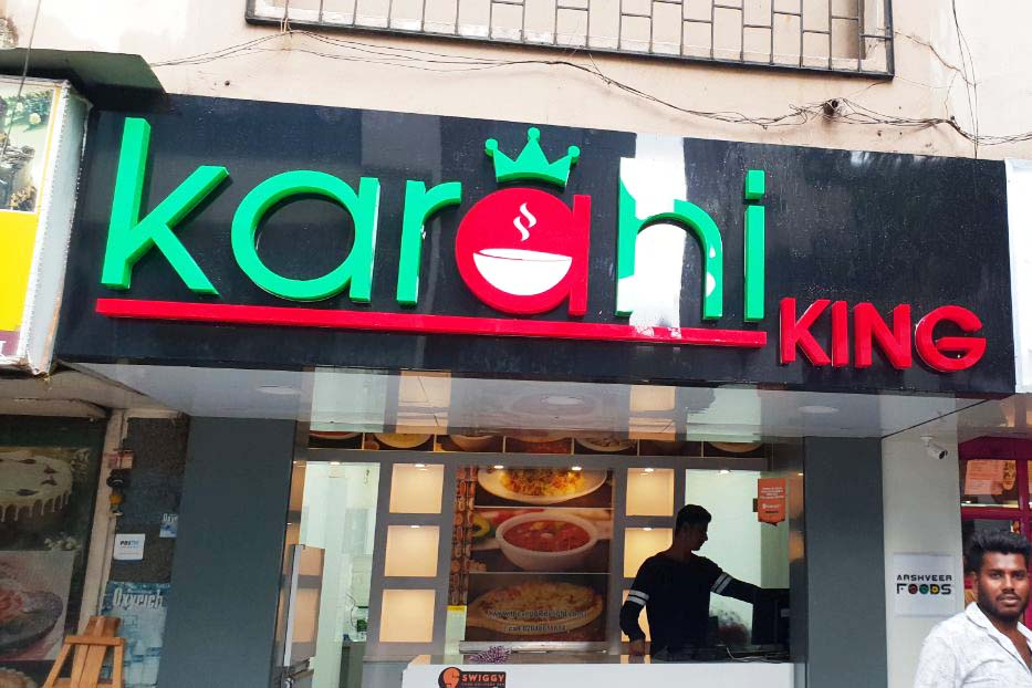 Thick letters made from green and red acrylic cut in the shape of the Karhai King logo mounted on a black ACP frame