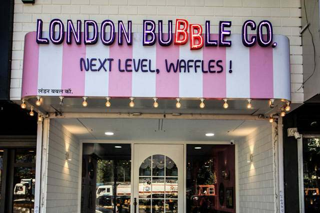 Colorful neon sign board created for the storefront of a waffles shop named the London Bubble Company
