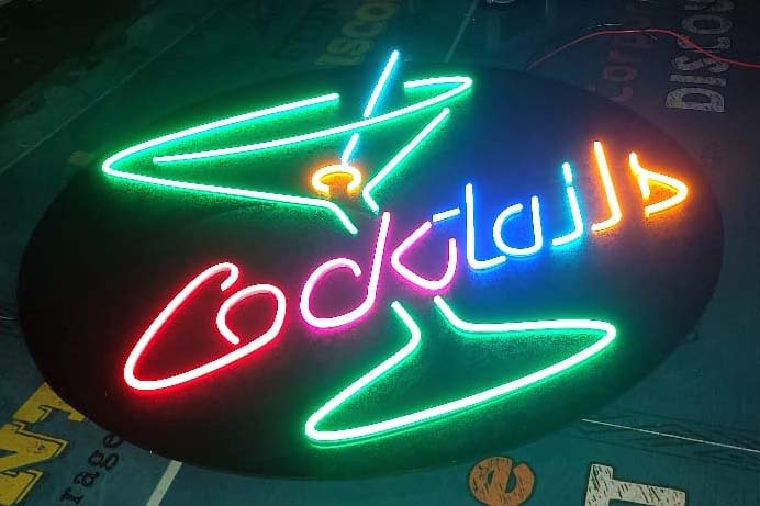 Brightly colored neon sign for a cocktail bar made out of neon lights of different colors and mounted on a black colored circular base