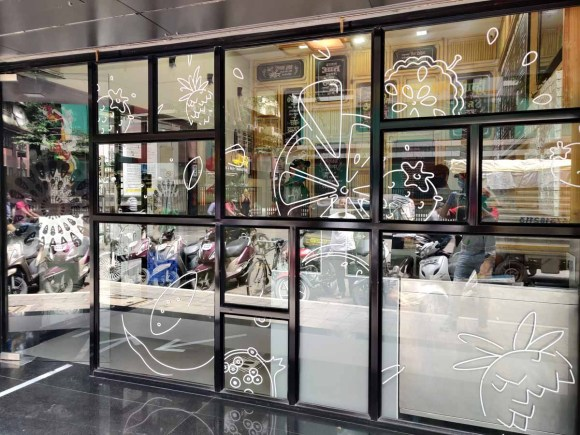 White ink printing of graphical designs and icons on the glass frontage of a restaurant