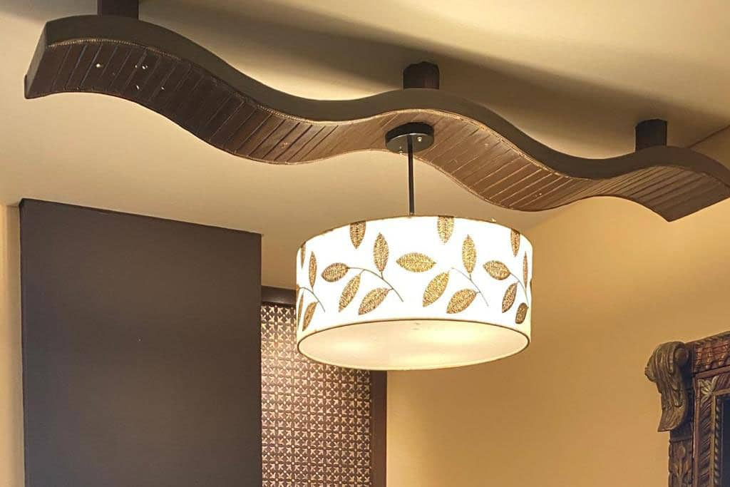 Here is a personalised lampshade suspended from the ceiling and carrying a custom design. A canvas print of a leaf pattern is wrapped around a hollow cylinder containing bright lights.