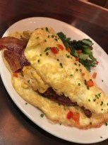 Shoo Mercy Omelet (Fried green tomato, smoked ham, bacon, pimento cheese, pickled jalapeño) at Tupelo Honey Cafe