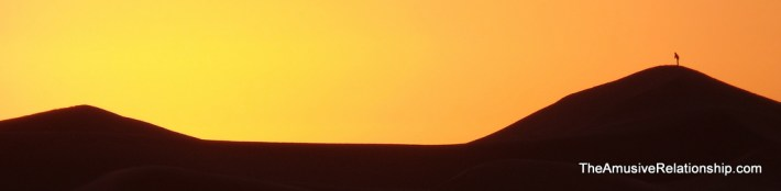 Sunrise in the desert with a distant figure atop a dune