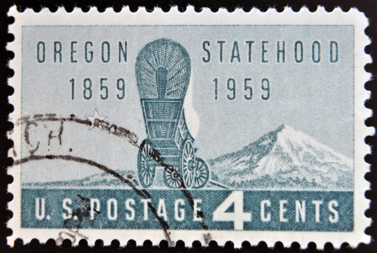 From the Sons and Daughters of Oregon Pioneers: A Stamp printed in 1959 for the Oregon Centennial shows a covered Wagon and Mount Hood Oregon