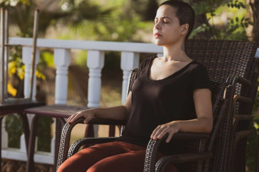 Woman in wicker chair on her front front porch practicing pranayama.