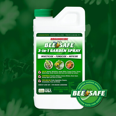 green and white pint container of bee safe organic pest garden spray concentrate twist on cap over green flower field