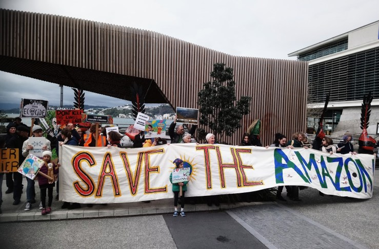 "Crowd shot opposite the Brazilian Embassy of about 30 people holding a colourful banner that reads ""Save the Amazon."""