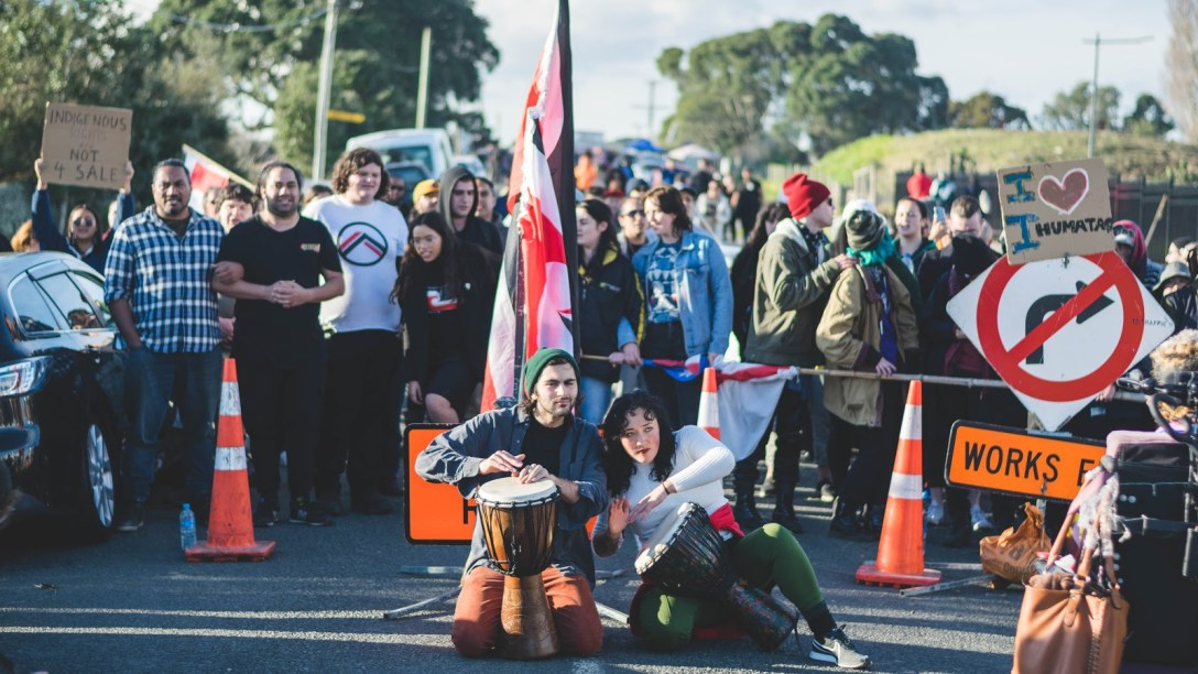 Southern barricade at Ihumātao depicts a vibrant crowd of people with arms linked. Road cones, roadworks signs, and tino rangatiratanga flags stand in front of the people. Two OA members play drums at the front.