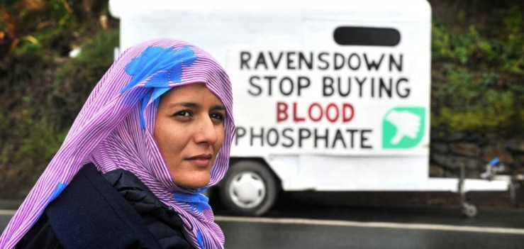 """Tecber Ahmed Saleh stands in front of a sign that reads """"Ravensdown Stop Buying Blood Phosphate."""""""