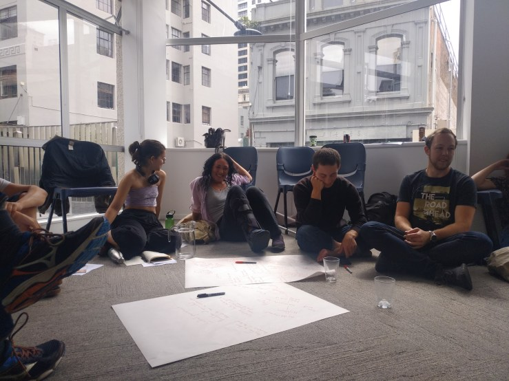 Members in Auckland engage with a workshop on Te Tiriti justice. 4 people sit on the carpet with pens and big sheets of paper spread out across the floor.