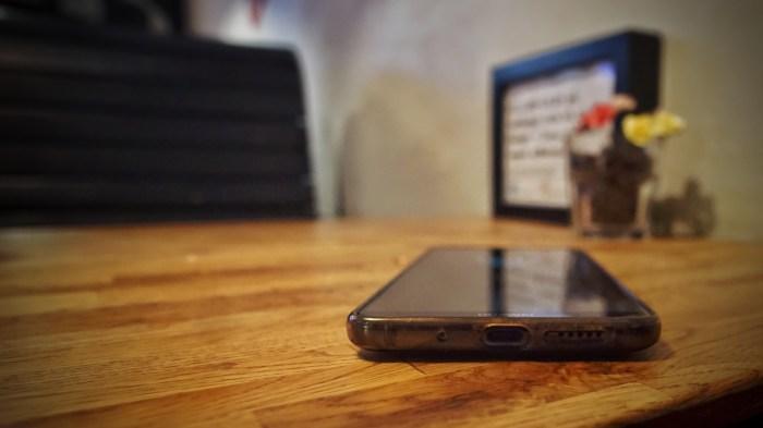 Min telefon, med det i texten omnämnda uttaget vänt mot kameran, på ett bord.