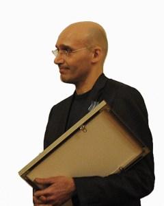 BIld på konstnären Walid Raad, hållandes vad som ser ut som en tavla eller möjligtvis plakett.
