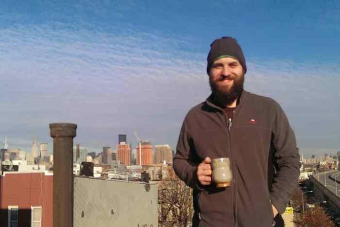 Jag på ett tak i New York, med en kaffemugg i handen och Manhattan i bakgruden och ett stort leende på läpparna.