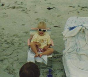 A toddler in a yellow shirt sits in a beach chair in the sand, wearing heart shaped sunglasses because she´s cute like that.