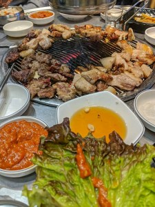 A table of meat and an open grill for a traditional Korean bbq in Seoul