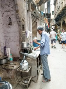 A man serves masala chai tea in the heart of Old Delhi
