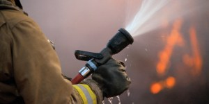 Spraying fire hose held by firefighter