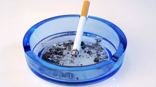 Cigarette burning in ashtray --- Image by © ImageShop/Corbis
