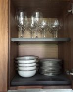 inside of kitchen cabinet showing wineglasses, plates and bowls