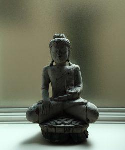 statue of seated buddha on windowsill