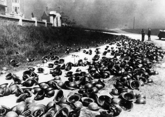 German soldiers examine helmets left on the beach by British and French soldiers near Dunkirk, 1940