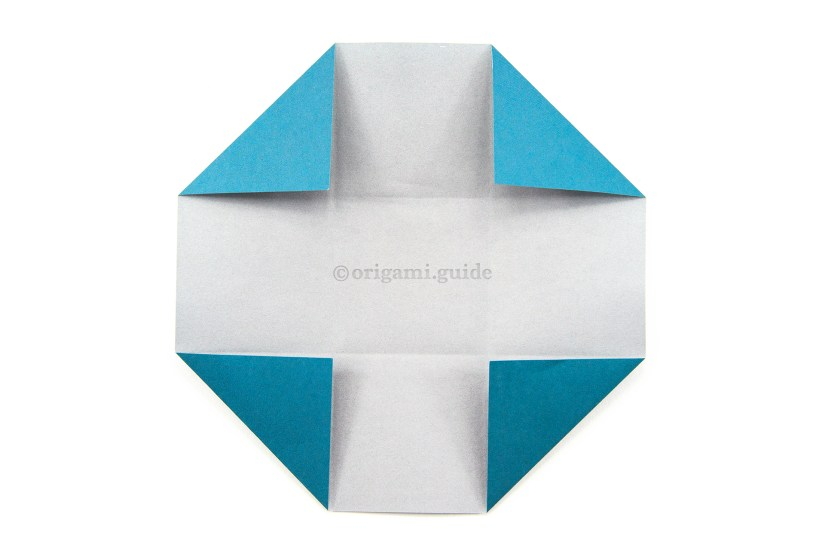 15. Fold all for corners diagonally inwards, aligning with the creases.