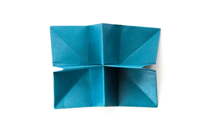 34. Fold the model backwards, the central vertical crease becoming a mountain fold.