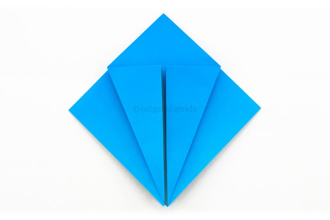 15. Fold the left and right lower diagonal edges inwards to align with central vertical crease.