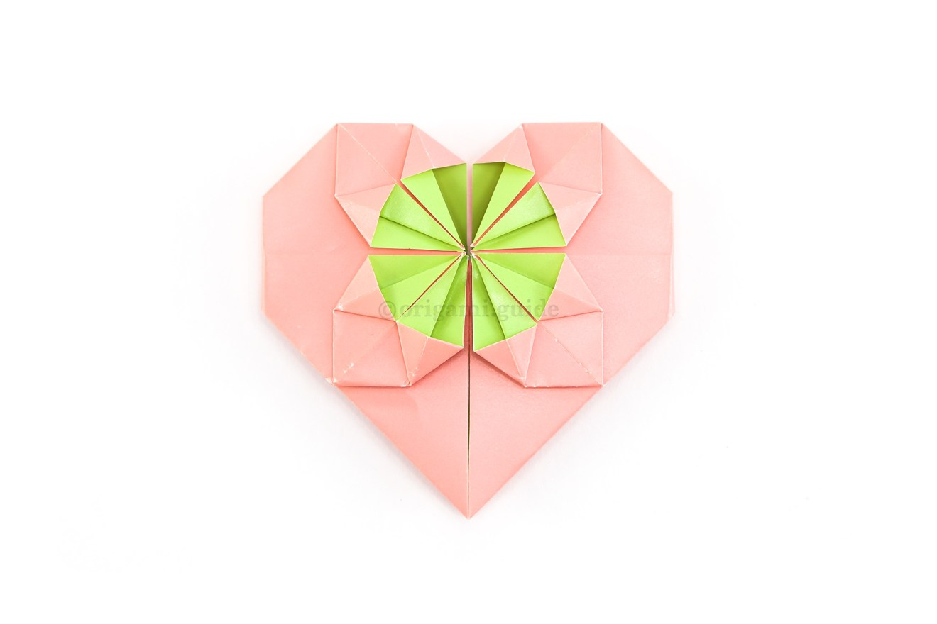 """32. The fancy origami heart is complete! If you're adding coin to the middle circle, it will fit under the four """"spikes"""" inside the circle."""