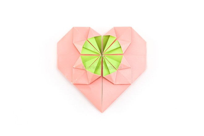 "32. The fancy origami heart is complete! If you're adding coin to the middle circle, it will fit under the four ""spikes"" inside the circle."