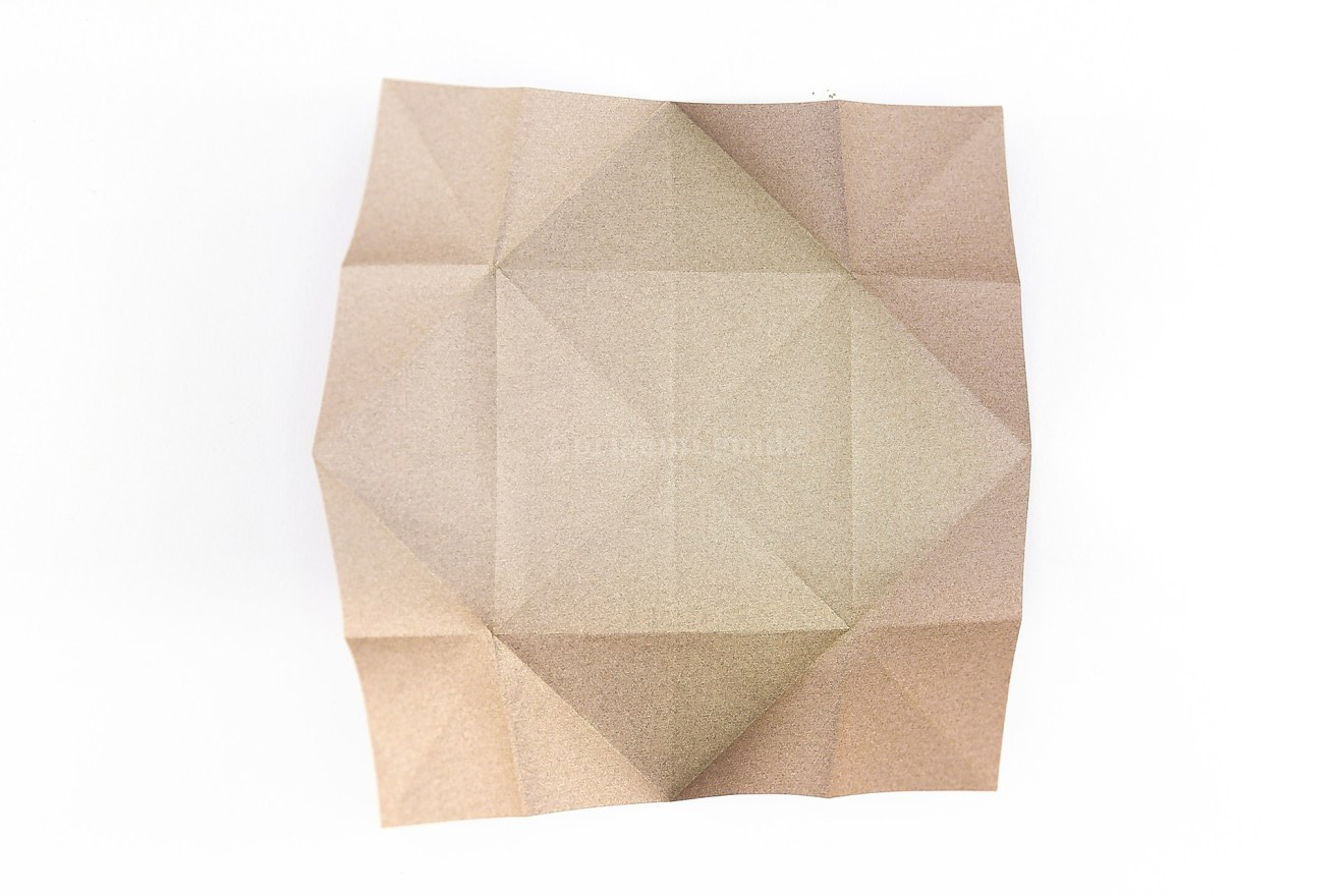 Flip the paper over to the back. So the corner flaps are angled up from the table.