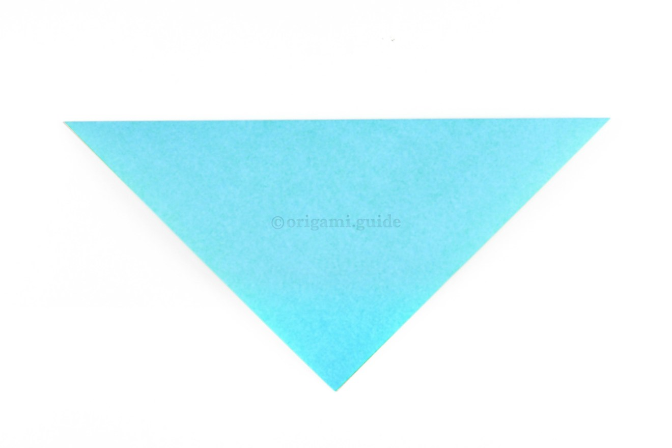 Fold the top corner down to the bottom corner to make a triangle.