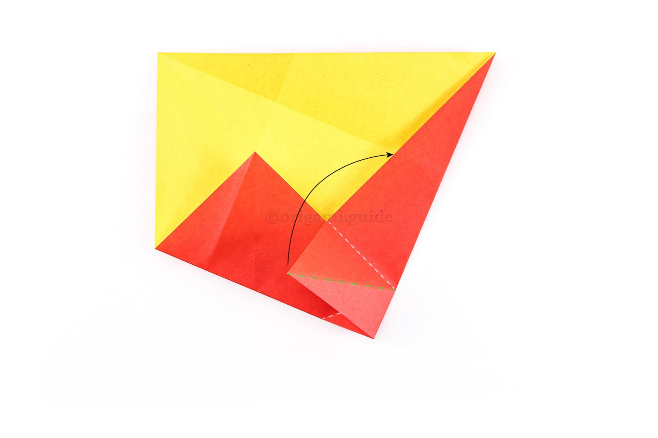 Take note of the lines and the arrow. The white dotted line indicates a valley fold, the green dot-dash line indicates a mountain fold. Bring the bottom left point of the flap up and across to the right. A new crease is created where the white valley folds are.