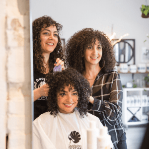 The image depicts three women in a hair salon called Original Moxie.