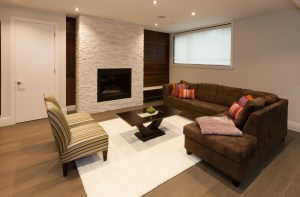 Basement Living Room Remodel with Fireplace and Full Height Stack Stone Surround bounded by stained wood panels