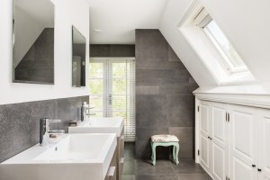 2nd Level Bathroom Remodel with Grey Stone Tile Floor and Walls, 2-Sinks and Low Eave Storage Cabinets on right hand side